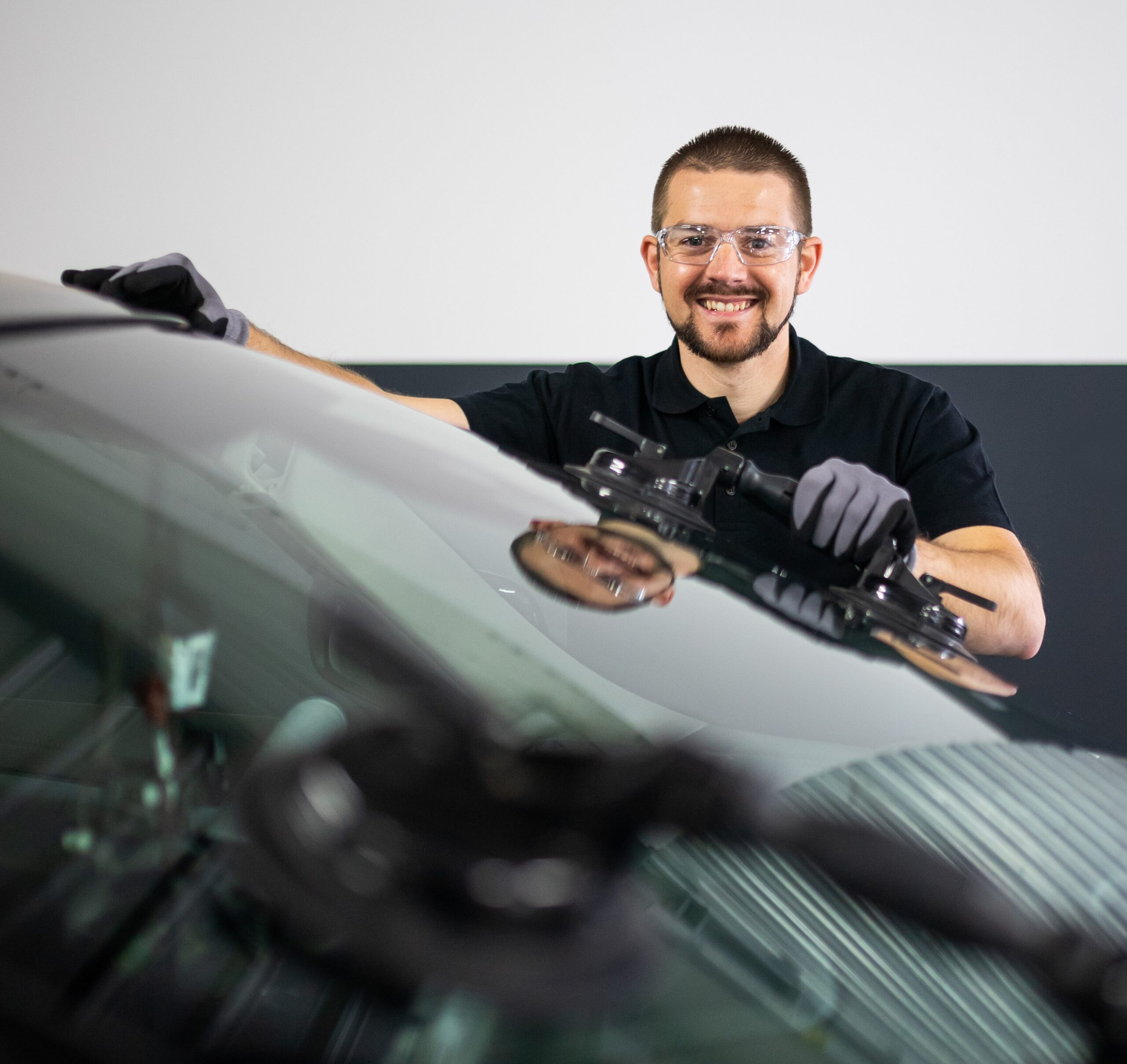 Changement d'un pare-brise a l'aide de ventouse par un technicien souriant 123 Pare-Brise