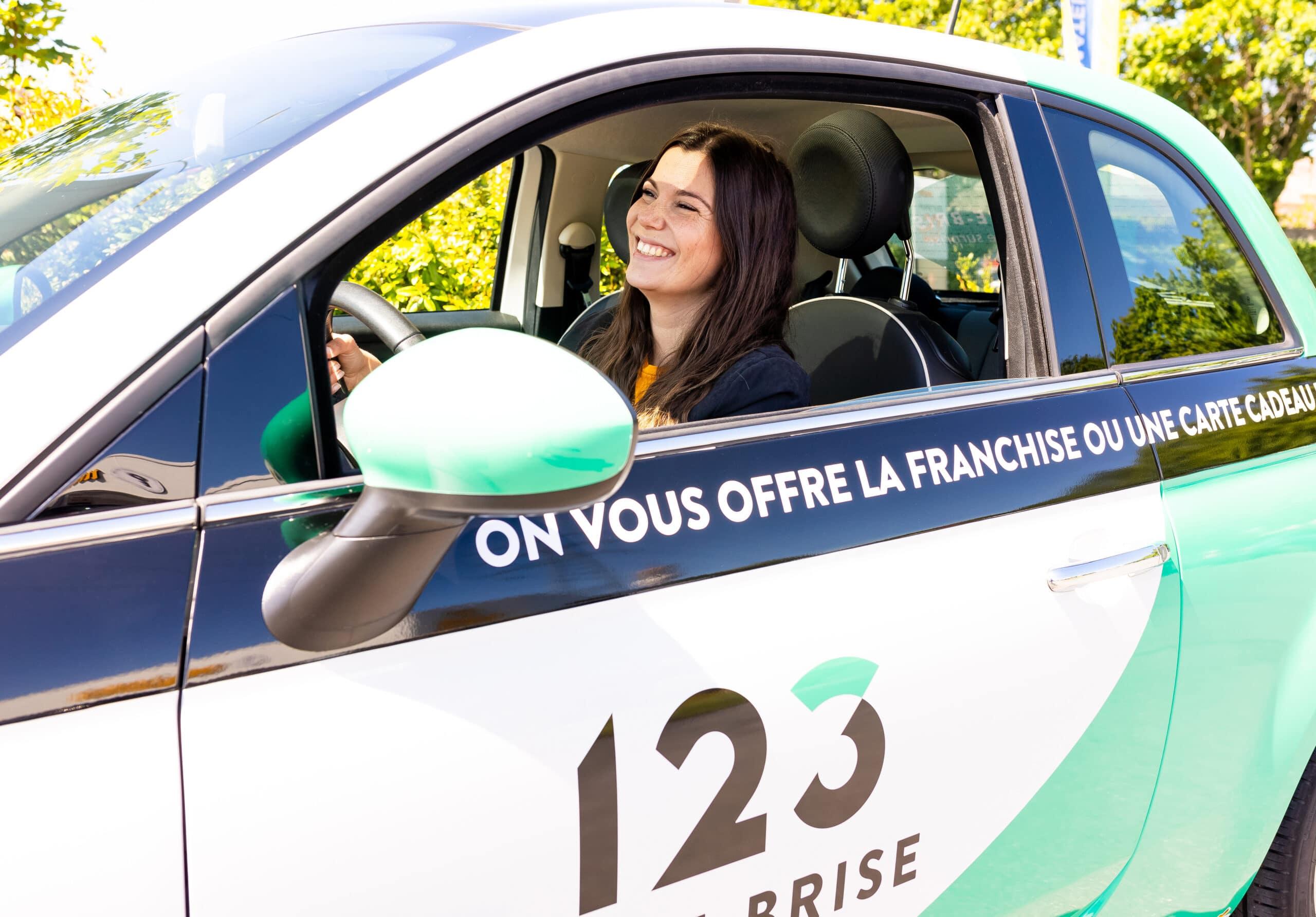 Cliente souriante a bord de notre vehicule de pret 123 Pare-Brise