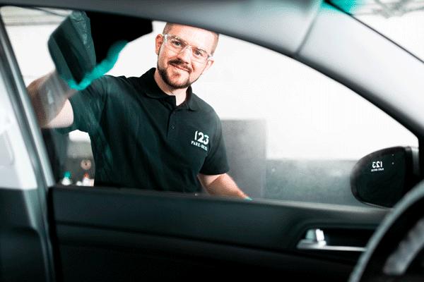 Nettoyage d'une vitre laterale de voiture par un technicien 123 Pare-Brise