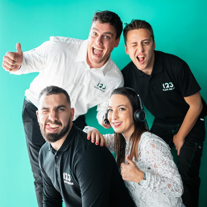 4 membres de l'équipe 123 Pare-Brise qui font une photo fun