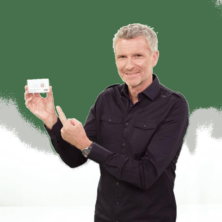 Denis Brogniart avec une carte cadeau Illicado de 150€ dans sa main