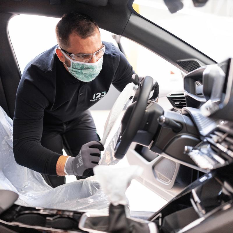 Un techncien vitrage 123 pare-brise nettoie le véhicule d'un client et désinfecte l'habitacle pour lutter contre la covid-19.